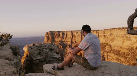 think big : Happy excited young adult tourist man sits on big rock watching incredible sunset scenery over Grand Canyon mountains.