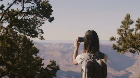dziki zachod : Back view happy young traveler woman hiking, taking smartphone photo of amazing Grand Canyon view scenery touching hair.