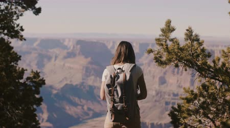 dziki zachod : Beautiful young happy tourist woman with backpack watching epic Grand Canyon mountains, walking back to camera.