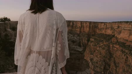 erosão : Slow motion camera moves behind happy young female tourist watching epic sunset Grand Canyon mountain reserve scenery.
