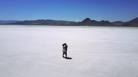 lélegzetelállító : Cinematic aerial shot of excited happy romantic couple walking together, hugging in epic salt lake desert landscape. Stock mozgókép