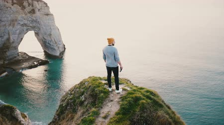 Нормандия : Camera spins around young happy Caucasian man standing at epic sunset ocean view on top of Normandy rocky shore cliff.