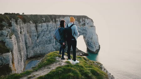 casal : Drone flying around young happy tourist couple with backpacks watching epic sunset sea on top of Normandy coast cliff.