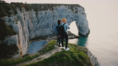casal : Drone moving around young happy friends standing together on top of sunset white coast cliff in Normandy watching view.