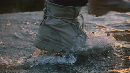 resistant : Close-up shot of male leg wearing grey waterproof desert shoe stepping right into water stream on sunset slow motion.