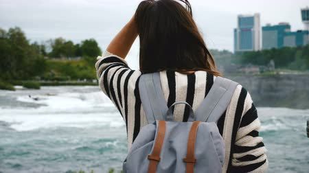 podkowa : Back view of happy young tourist woman with backpack watching rushing water at Niagara Falls waterfall slow motion. Wideo