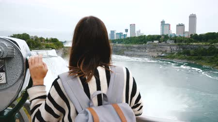 binocolo : Camera slides behind happy tourist woman with one hand on coin operated binoculars at epic Niagara waterfall slow motion Filmati Stock