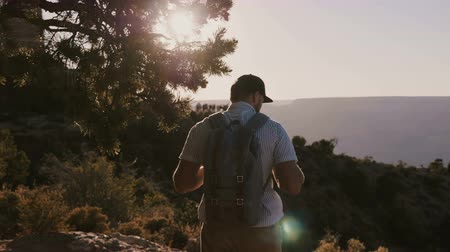 wanderlust : Camera follows happy active young tourist man hiking with backpack, watching epic summer sunset scenery of Grand Canyon.