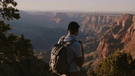 dziki zachod : Slow motion happy young businessman with backpack hiking on vacation at epic summer sunset panorama of Grand Canyon.