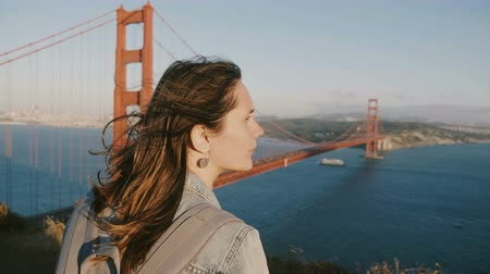 невероятный : Peaceful young tourist woman with hair blowing in strong wind enjoying epic sunset panorama at iconic Golden Gate Bridge