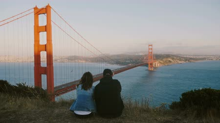 icônico : Back view happy man and woman sit close together watching epic beautiful view of Golden Gate Bridge in San Francisco. Vídeos