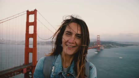 brackets : Amazing lifestyle portrait of happy tourist woman with hair blowing in strong wind at famous sunset Golden Gate Bridge.