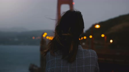Франциско : Back view young woman standing alone in late evening watching iconic Golden Gate Bridge traffic view under strong wind.