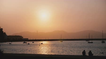 embarcadero : Beautiful romantic sunset panorama of misty San Francisco pier, boats and tourists with Golden Gate bridge in background