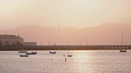embarcadero : Beautiful background shot of romantic misty San Francisco sunset pier with boats and birds, sun reflecting in sea water.