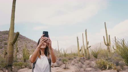 sudoeste : Slow motion camera moves around young happy tourist woman taking smartphone photo in cactus desert at USA national park.