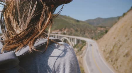průhled : Close-up back view shot of young woman with hair flying in the wind enjoying view of Highway One at Bixby bridge Big Sur Dostupné videozáznamy
