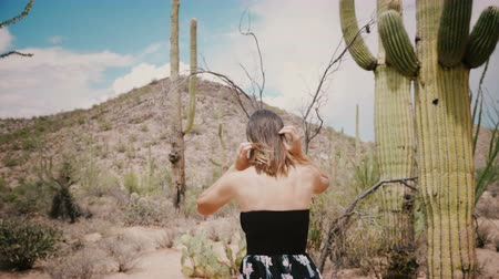 southwest : Slow motion camera follows young local woman in black dress walking at summer cactus desert national park in Arizona USA Stock Footage