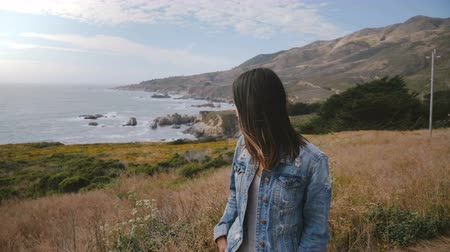 olhando para baixo : Young beautiful sad woman looks depressed and down walking on epic Big Sur ocean coast covered with lush yellow flowers.