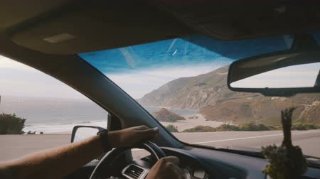 vibes : Atmospheric POV shot of man driving along incredible sunny ocean coast road with mountain view at Big Sur California.