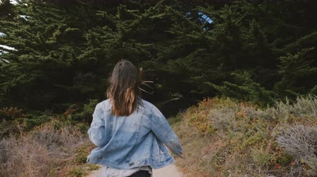 positive vibes : Camera follows beautiful young happy free woman running with arms open on a small path into dark forest at Big Sur.