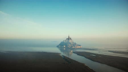 Нормандия : Atmospheric cinematic aerial shot of foggy sunrise Mont Saint Michel on high tide, famous island fortress in Normandy.