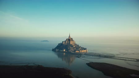 éteri : Drone flying towards epic sunrise Mont Saint Michel, famous island fortress castle surrounded by foggy sea in Normandy. Stock mozgókép