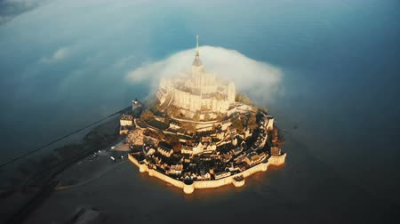 irreal : Aerial top view, drone rising above sunrise Mont Saint Michel island castle with a big cloud above it in Normandy France
