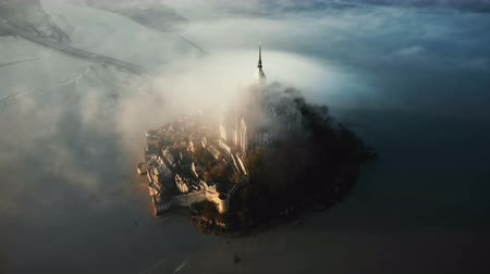 épico : Drone flying high around amazing Mont Saint Michel island castle fortress covered with massive sunrise fog clouds flow.