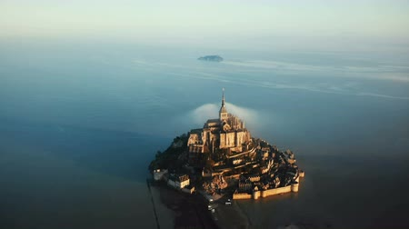 mystik : Cinematic aerial shot of ethereal sunrise Mont Saint Michel island castle surrounded by high tide sea in Normandy France