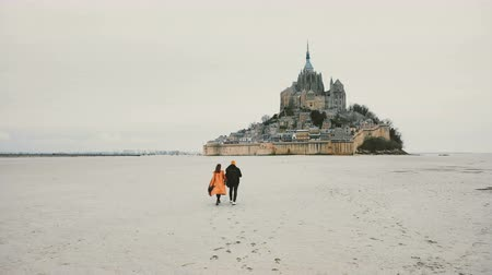 Нормандия : Beautiful cinematic shot, drone follows young happy couple walking towards Mont Saint Michel fortress in Normandy France