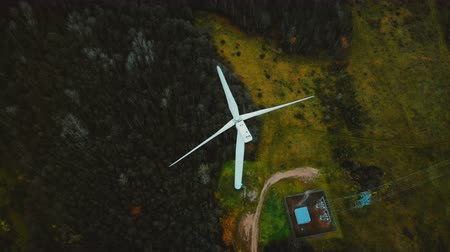 humanity : Beautiful aerial top view of working windmill turbine in the middle of lush green forest, alternative sustainable energy
