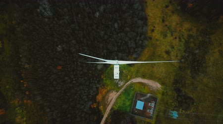 sustainable resources : Static top view drone shot, windmill turbine spinning in the middle of green forest, alternative energy source concept.