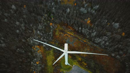 humanity : Drone moves backwards, tilts up revealing windmill turbine working in winter forest, renewable energy future concept.