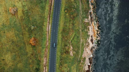 erodida : Top view aerial tracking shot of black car driving along atmospheric autumn coastline road, beautiful eroded sea shore Stock Footage