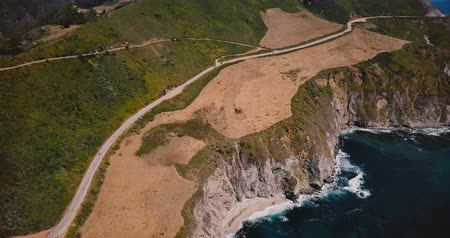 icônico : Drone panning left over amazing Highway 1 and beautiful Pacific Ocean sunny shore scenic view in Big Sur California. Vídeos