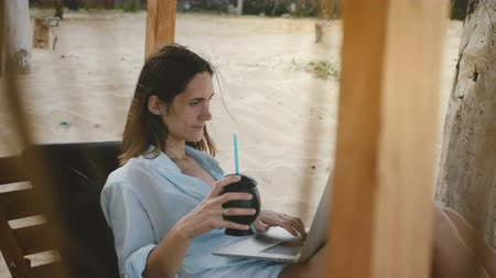 cadeiras : Happy beautiful successful female freelance worker enjoying drink while working at laptop mobile office on exotic beach.