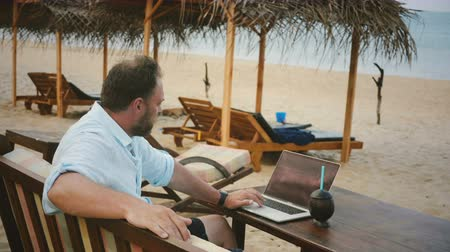 buying online : Back view POV shot of successful relaxed male freelancer using laptop in lounge chair on exotic summer resort beach.