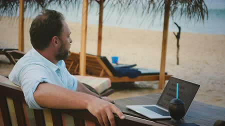 содержание : Medium shot of successful content businessman sitting in exotic beach lounge chair with laptop relaxing at ocean resort.