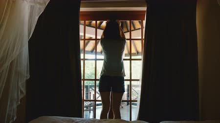 faház : Back view beautiful young happy woman opening hotel chalet curtains and window door, walk out to amazing sunny terrace.
