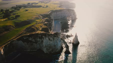 Нормандия : Drone flying high above famous white chalk seaside cliffs and arches, pastoral green sunset fields at Etretat Normandy.