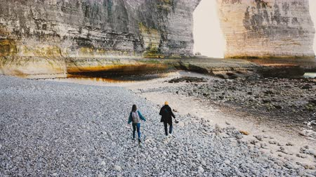 erosão : Drone camera follows happy tourist man and woman walking along beautiful big pebble beach to majestic rocks in Normandy.