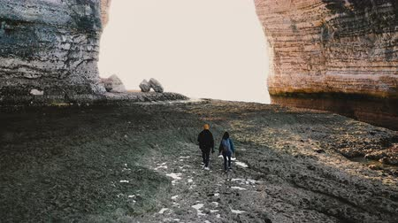 laagtij : Drone follows happy tourist couple walk along incredible alabaster low tide sea beach under epic giant arch in Normandy.