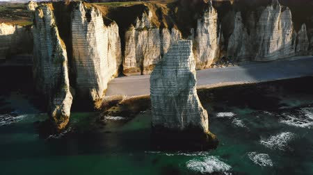 normandiya : Drone flying above epic natural alabaster rock arch and pillar at famous white seaside cliffs of sunny Etretat Normandy. Stok Video