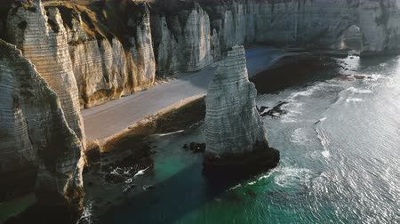 normandiya : Drone panning above incredible natural eroded rock arch and pillar at famous white alabaster sea cliffs at Etretat. Stok Video