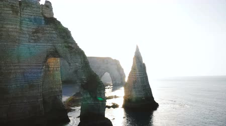 erodált : Beautiful backlight drone panorama, giant natural eroded rock arch and pillar at famous white sea cliffs in Normandy. Stock mozgókép