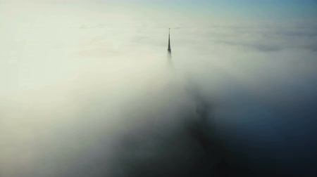 templomtorony : Drone flying above beautiful clouds around epic heavenly castle steeple top of Mont Saint Michel fortress in Normandy. Stock mozgókép