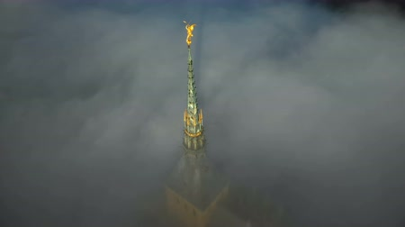 michael : Atmospheric aerial close-up shot of glowing golden statue on top of Mont Saint Michel castle steeple above dark clouds.