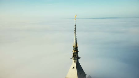 michael : Drone flying around amazing golden abbey spire of Mont Saint Michel fortress castle glowing in the sun above clouds.