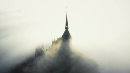 irreal : Aerial shot, fog clouds flowing over famous majestic Mont Saint Michel fortress castle during epic sunrise in Normandy.
